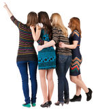 Back view of group beautiful women pointing at wall. Royalty Free Stock Images