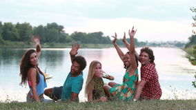 Back view of group of friends, turning around and waving to camera stock footage