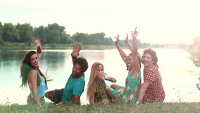 Back view of group of friends, turning around and waving to camera. Back view of the group of five young friends sitting on grass, turning around smiling and stock video footage