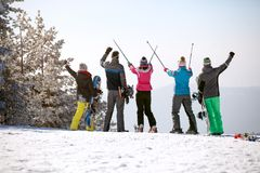 Back view of group skiers with ski sticks up in mountain. Back view of group male and female skiers with ski sticks up in mountain Stock Images