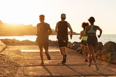 Back view of group sports people running outdoors royalty free stock image