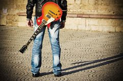 Back view of a guitarist standing with a guitar royalty free stock photo