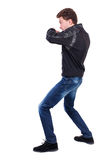 Back view of guy funny fights waving his arms and legs. Isolated over white background. Rear view people collection.  backside view of person.  Curly guy in a Royalty Free Stock Image