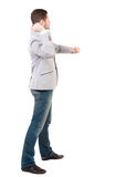 Back view of guy funny fights waving his arms and legs. Isolated over white background. Rear view people collection.  backside view of person. A guy in a gray Royalty Free Stock Photography