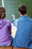 Explanation of formula. Back view of guy pointing at blackboard while explaining formula to girl stock photos