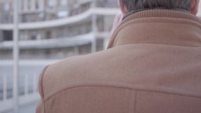 Back view of handsome confident man in brown coat walking on the city street talking by mobile phone. Urban cityscape in. Back view of handsome confident man in stock video