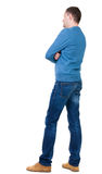 Back view of handsome man in blue pullover looking up. Standing young guy in jeans. Rear view people collection.  backside view of person.  Isolated over Stock Photography