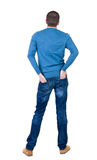 Back view of handsome man in blue pullover looking up. Stock Photos
