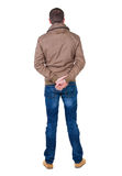 Back view of handsome man in brown windcheater looking up. Royalty Free Stock Photos