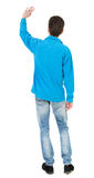 Back view of handsome man greeting waving from his hands Stock Photography