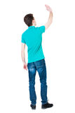 Back view of handsome man greeting waving from his hands. Royalty Free Stock Photo