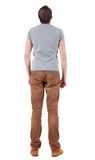 Back view of handsome man in shirt and jeanst  looking up. Stock Images