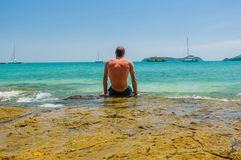Back view of a handsome man sitting on the stone and looking on the boats in the sea l. Selective focus on tired male on. Back view of handsome man sitting on Royalty Free Stock Image