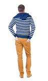 Back view of handsome man in striped hooded sweater. Stock Photo