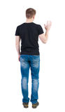 Back view of handsome man in t-shirt  greeting waving from his h Royalty Free Stock Photo