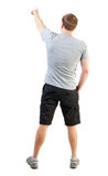 Back view of handsome man in t-shirt and  shorts pointing Stock Image