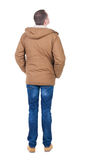 Back view of handsome man in winter jacket  looking up. Standing young guy in parka. Rear view people collection.  backside view of person.  Isolated over Royalty Free Stock Photography