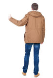 Back view of handsome man in winter jacket  shows thumbs up. Standing young guy in parka. Rear view people collection.  backside view of person.  Isolated over Royalty Free Stock Photography