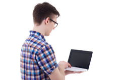 Back view of handsome teenage boy holding laptop with blank scre Stock Photo