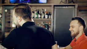 Back view of young man with tattoed hands dressed in black t-shirt walking through the cafe to his friends. Two women. Back view of handsome young man with stock footage