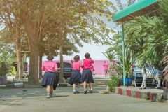 Back view of happiness primary girl students in pink shirt and blue skirt walk to classrooms royalty free stock photography