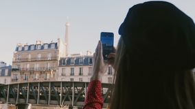 Back view happy beautiful tourist woman taking smartphone photo of Eiffel Tower view in Paris from apartment balcony. stock video footage
