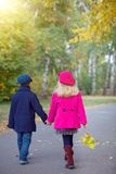 Children walking in beautiful autumn park on warm sunny fall day. Back view of happy children walking in beautiful autumn park on warm sunny fall day Royalty Free Stock Images