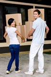 Back view of couple carrying cardboard containers Stock Photo