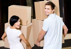 Back view of couple carrying pasteboard containers Stock Image