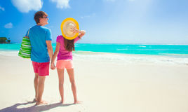 Back view of happy couple iwith beach bag on the Stock Images