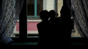 Back View of Happy Family Hugging Near the Window. Silhouette of the Mother, Father and Their Little Daughter with Two