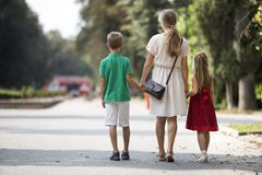 Back view of happy family, young blond long-haired woman walking holding hands with two children, small daughter and son along royalty free stock images