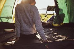 Back view of happy female tourist relaxing in camping tent with. Mountain and sun flare background. People and lifestyles concept. Travel and vacation in stock photography
