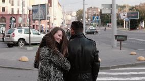 Back view of happy lovers walking in the street. Beautiful girl looks back into camera smiling. Slow mo, steadicam shot. Back view of happy lovers walking in the stock video footage