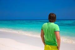 Back view of happy man enjoying good life on exotic beach, guy l royalty free stock photo