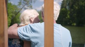 Back view of a happy mature couple sitting on the bench near the river, admiring nature. Senior woman kissing her. Back view of happy mature couple sitting on stock footage