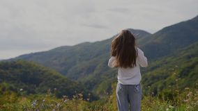 Back view of happy teenage girl on top of mountains. stock video
