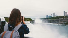 Back view of happy traveler woman with backpack and camera taking photo of amazing Niagara Falls waterfall slow motion. Professional female photographer stock footage