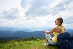Woman hiker hiking on grassy hill, wearing backpack, using trekking sticks in the mountains. Back view of happy woman backpacker sitting and resting on grassy royalty free stock image