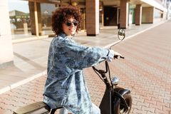 Back view of happy woman in sunglasess sitting on motorbike Royalty Free Stock Image