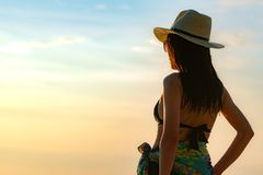 Back view of happy young Asian woman in black swimsuit and straw hat relax and enjoy holiday at tropical paradise beach at sunset. royalty free stock photos