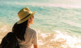 Back view of happy young Asian woman in casual style fashion with straw hat and backpack. Relax and enjoy holiday at tropical stock images