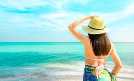 Back view of happy young Asian woman with straw hat relax and enjoy holiday at tropical paradise beach. Girl in summer vacation royalty free stock images