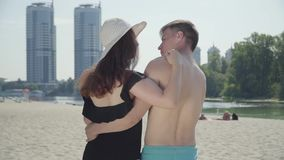 Back view of happy young couple hugging and looking at each other with love. Lovers enjoying weekends at hot sunny stock video