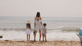 Back view happy young mother with little boy and girl watching the waves on vacation at tropical sea beach slow motion. stock video footage