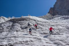 back view of hikers climbing at beautiful snow capped mountains, kyrgyzstan, stock photos