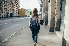 Back view of a hipster girl walking on city street. royalty free stock images