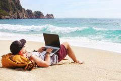 Young man in tank top, shorts, snapback cap at beach with laptop & backpack. Freelancer, hipster blogger, writer enjoying sea view. Back view, hipster young man royalty free stock images
