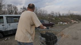 Back view of male pushing shopping cart at landfill. Back view of homeless male walking at landfill site with garbage and old abandoned cars, pushing cart with stock video