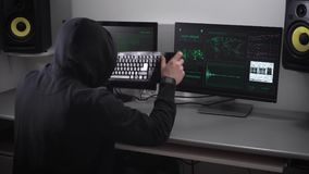 Back view of a hooded angry hacker in black making cyber attack on bank network and failuring the process. Aggravated stock video footage